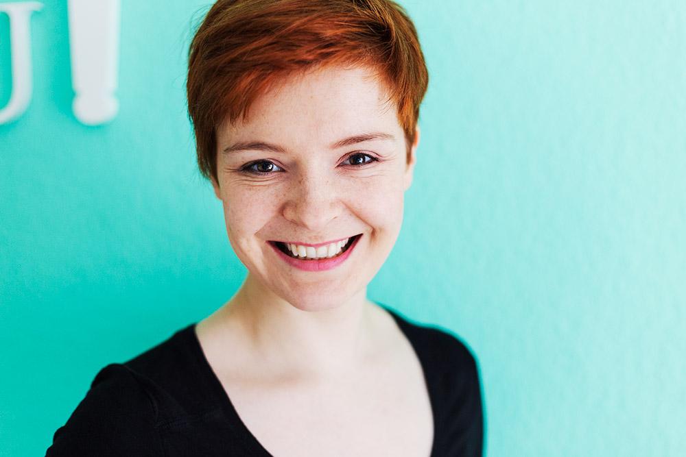 Schauspielerportrait einer Frau vor einer blauen Wand